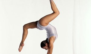 Young female gymnast on balance beam performing, side view